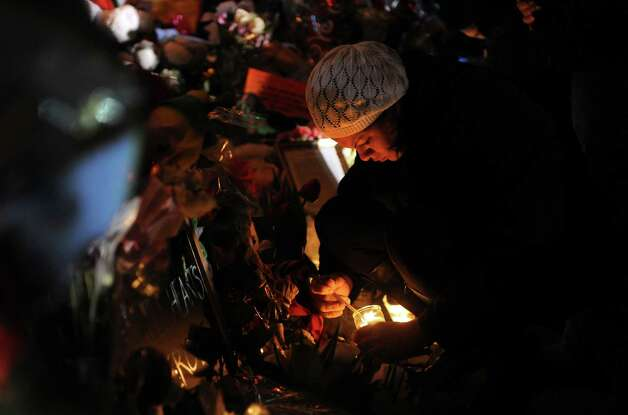 Yolanda Velez, of Bridgeport, lights a candle at a memorial for shooting victims near Sandy Hook Elementary School Wednesday, Dec. 19, 2012 in Newtown, Conn. Photo: Autumn Driscoll / Connecticut Post