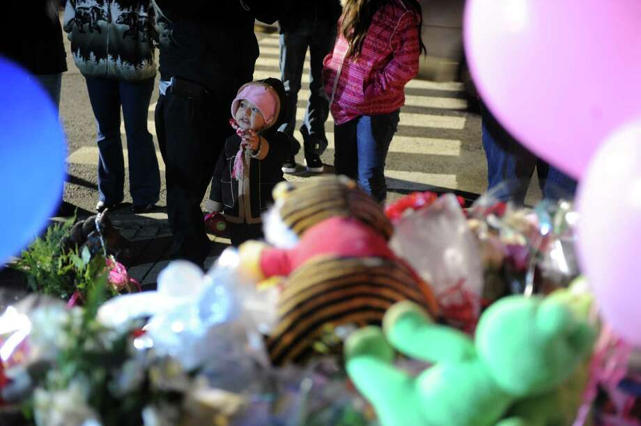 A toddler stands with her parents as they say a prayer at a memorial for shooting victims near Sandy Hook Elementary School Wednesday, Dec. 19, 2012 in Newtown, Conn. Photo: Autumn Driscoll / Connecticut Post