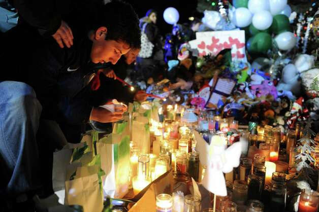 Mourners light candles and say prayers at a memorial for shooting victims near Sandy Hook Elementary School Wednesday, Dec. 19, 2012 in Newtown, Conn. Photo: Autumn Driscoll / Connecticut Post
