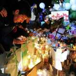 Mourners light candles and say prayers at a memorial for shooting victims near Sandy Hook Elementary School Wednesday, Dec. 19, 2012 in Newtown, Conn.