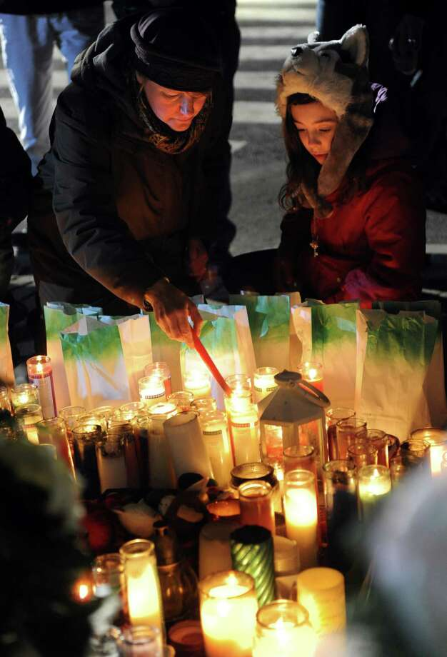 Allison Plous, of Higganum, and her 10-year-old daughter, Fijare, light candles in front of a memorial for shooting victims near Sandy Hook Elementary School Wednesday, Dec. 19, 2012 in Newtown, Conn.  The Plous family was on their way to visit relatives out of state and wanted to stop in Newtown to pay their respects to the victims of last week's mass shooting. Photo: Autumn Driscoll / Connecticut Post