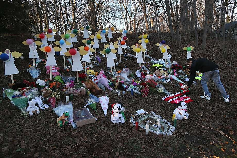 NEWTOWN, CT - DECEMBER 19:  A man places a plush santa at a makeshift memorial for Sandy Hook shooting victims on December 19, 2012 in Newtown, Connecticut. Adam Lanza reportedly shot his mother Nancy Lanza last Friday before he killed 26 others, including 20 children, at Sandy Hook Elementary School.  (Photo by John Moore/Getty Images) Photo: John Moore, Getty Images