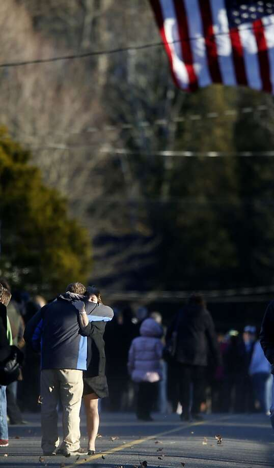 Mourners embrace before lining up to enter the calling hours for Sandy Hook Elementary School principal Dawn Lafferty Hochsprung, Wednesday, Dec. 19, 2012, in Woodbury, Conn.  Hochsprung was killed when a gunman forced his way into Sandy Hook Elementary School in Newtown on Dec. 14 and opened fire, killing 26 people, including 20 children. (AP Photo/Jason DeCrow) Photo: Jason DeCrow, Associated Press
