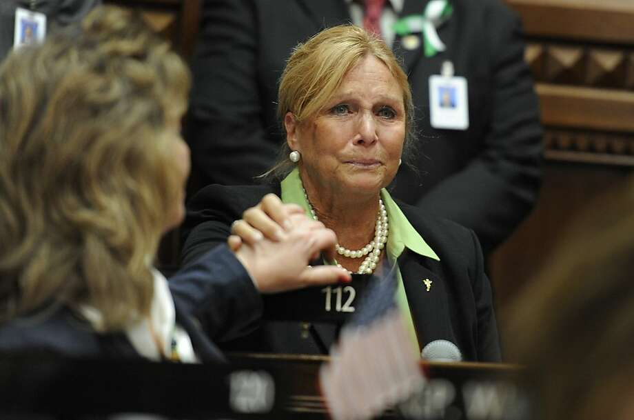 State Rep. DebraLee Hovey, R-112 district, including Newtown, grabs the hand of colleague Rep. Laura Hoydick, R-Stratford, left, after speaking at a memorial service for the victims of the Sandy Hook Elementary School shooting before the House of Representatives and Senate meet for special session the state Capitol in Hartford, Conn., Wednesday, Dec. 19, 2012. (AP Photo/Jessica Hill) Photo: Jessica Hill, Associated Press