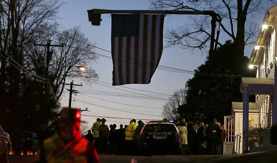 Mourners wait under a giant American flag outside the funeral home hosting the wake of Sandy Hook Elementary School principal Dawn Lafferty Hochsprung in Woodbury, Conn., Wednesday, Dec. 19, 2012. A gunman opened fire killing 26 people, including the principal and 20 children, at the school in Newtown before killing himself on Dec. 14. (AP Photo/Charles Krupa) Photo: Charles Krupa, Associated Press