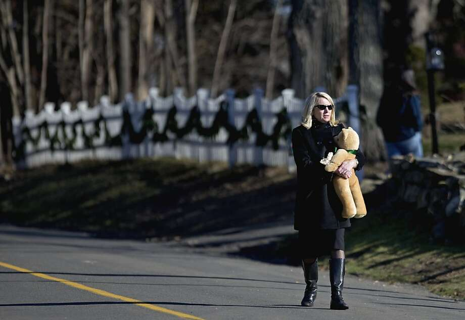 A mourner holds a teddy bear as she walks to visit a memorial to the Sandy Hook Elementary School shooting victims outside the school's entrance, Wednesday, Dec. 19, 2012, in Newtown, Conn. (AP Photo/David Goldman) Photo: David Goldman, Associated Press