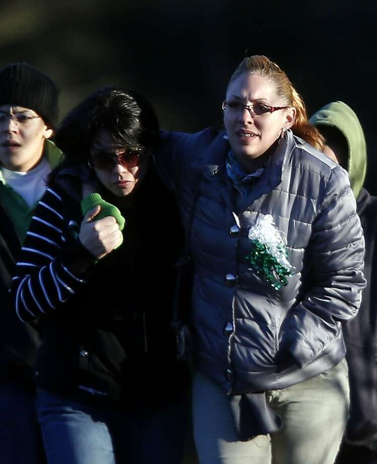 Mourners wear green and white ribbons as they arrive for the calling hours of Sandy Hook Elementary School principal Dawn Lafferty Hochsprung, Wednesday, Dec. 19, 2012, in Woodbury, Conn.  Hochsprung was killed when a gunman forced his way into Sandy Hook Elementary School in Newtown on Dec. 14 and opened fire, killing 26 people, including 20 children. (AP Photo/Jason DeCrow) Photo: Jason DeCrow, Associated Press