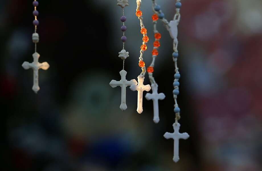 Rosaries are lit by the morning light on a makeshift memorial near the town Christmas tree in the Sandy Hook village of Newtown, Conn., Wednesday, Dec. 19, 2012. The memorial, which was put up in the aftermath of the elementary school shooting that shocked the small town, is increasing in size as the days go on. More funerals are scheduled for Wednesday, as the town continues to mourn its victims. The gunman, Adam Lanza, walked into Sandy Hook Elementary School in Newtown, Conn., on Dec. 14, and opened fire, killing 26 people, including 20 children, before killing himself. (AP Photo/Julio Cortez) Photo: Julio Cortez, Associated Press