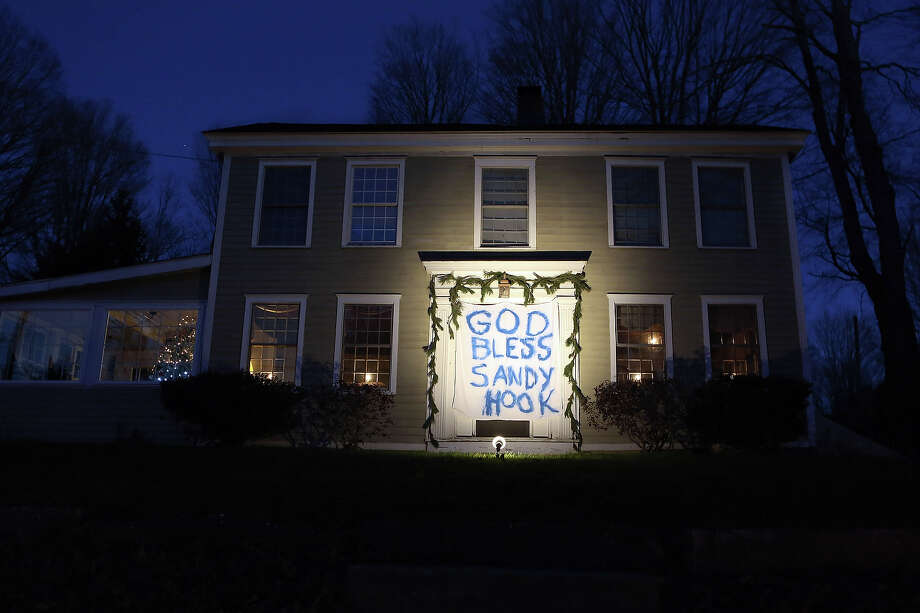 "NEWTOWN, CT - DECEMBER 19:  A banner that reads, ""God Bless Sandy Hook,"" stretches across the front door of a home on December 19, 2012 in Newtown, Connecticut. Adam Lanza reportedly shot his mother Nancy Lanza last Friday before he killed 26 others, including 20 children, at Sandy Hook Elementary School. Photo: John Moore, Getty Images / 2012 Getty Images"