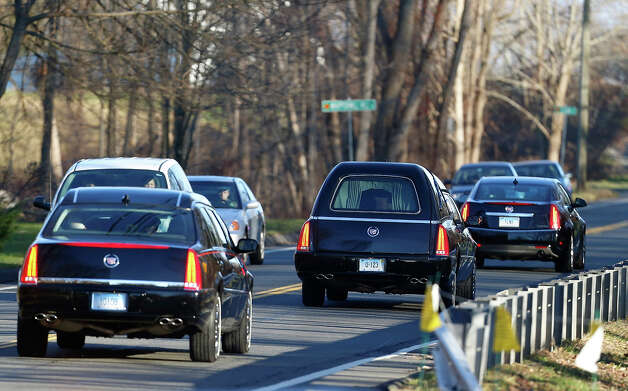 A hearse, center, drives in a procession following funeral services for Charlotte Helen Bacon, one of the students killed in the Sandy Hook Elementary School shooting last week, at Christ the King Lutheran Church, Wednesday, Dec. 19, 2012, in Newtown, Conn. The gunman, Adam Lanza, walked into Sandy Hook Elementary School in Newtown on Dec. 14 and opened fire, killing 26 people, including 20 children, before killing himself. Photo: AP