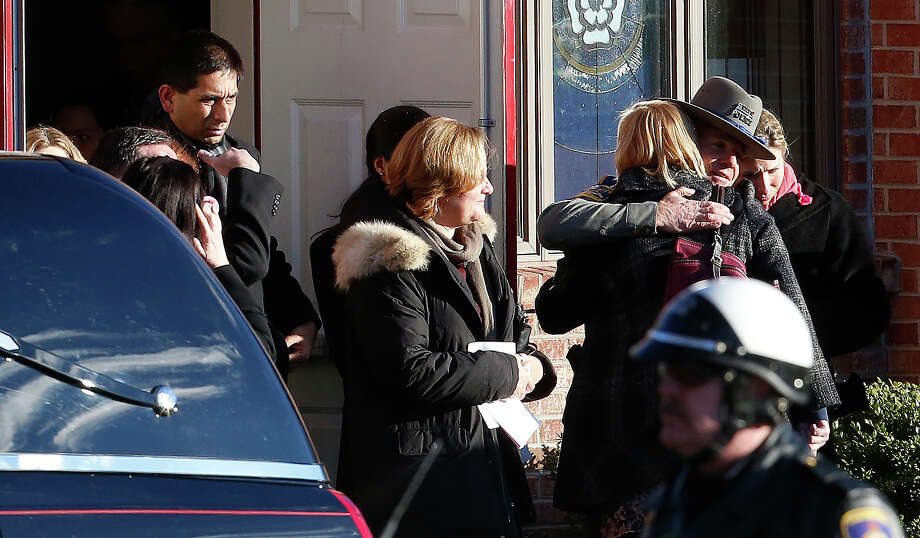 A deputy, center right, is embraced by a woman following funeral services for Charlotte Helen Bacon, one of the students killed in the Sandy Hook Elementary School shooting, at Christ the King Lutheran Church, Wednesday, Dec. 19, 2012, in Newtown, Conn. The gunman, Adam Lanza, walked into Sandy Hook Elementary School in Newtown, Conn. on Dec. 14 and opened fire, killing 26 people, including 20 children, before killing himself. Photo: AP