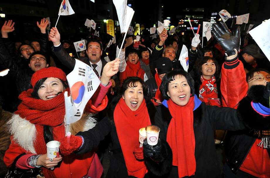 Supporters of South Korea's presidential candidate Park Geun-Hye of the ruling New Frontier Party, react as they watch live TV outside the party's office in Seoul on December 19, 2012.  South Korea appeared to have elected its first female president on December 19, as national TV predicted a clear victory for conservative Park Geun-Hye, daughter of the country's former dictator.  AFP PHOTO / JUNG YEON-JEJUNG YEON-JE/AFP/Getty Images Photo: Jung Yeon-je, AFP/Getty Images