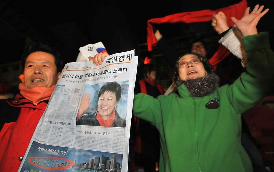 A supporter of South Korea's president-elect Park Geun-Hye of the ruling New Frontier Party holds up a newspaper with the front page showing Park's victory in Seoul on December 20, 2012.  South Korea elected its first female president on December 19, handing a slim but historic victory to conservative ruling party candidate Park Geun-Hye, daughter of the country's former military ruler.  AFP PHOTO / CHOI WON SUKCHOI WON SUK/AFP/Getty Images Photo: Choi Won Suk, AFP/Getty Images