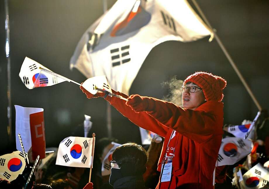 A supporter of South Korea's presidential candidate Park Geun-Hye of the ruling New Frontier Party waves national flags during her election campaign in Seoul on December 18, 2012. The two rivals for South Korea's presidency made a final pitch to voters on the eve of an election that looks set to go down to the wire and could produce the country's first female leader.  AFP PHOTO / JUNG YEON-JEJUNG YEON-JE/AFP/Getty Images Photo: Jung Yeon-je, AFP/Getty Images