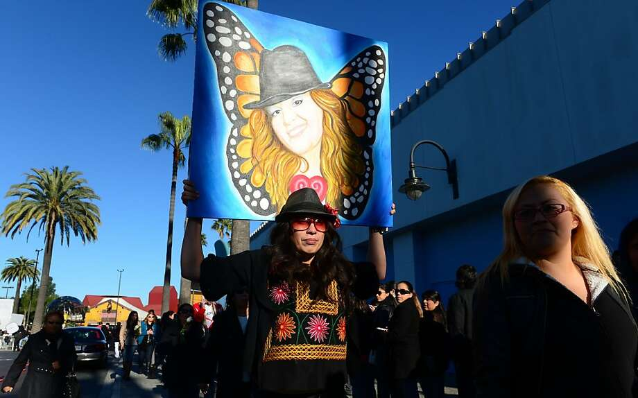 A woman, carrying a painting of Mexican American singer Jenni Rivera, waits in line to attend a memorial service for the singer, who died with six other people in a plane crash. Photo: Frederic J. Brown, AFP/Getty Images