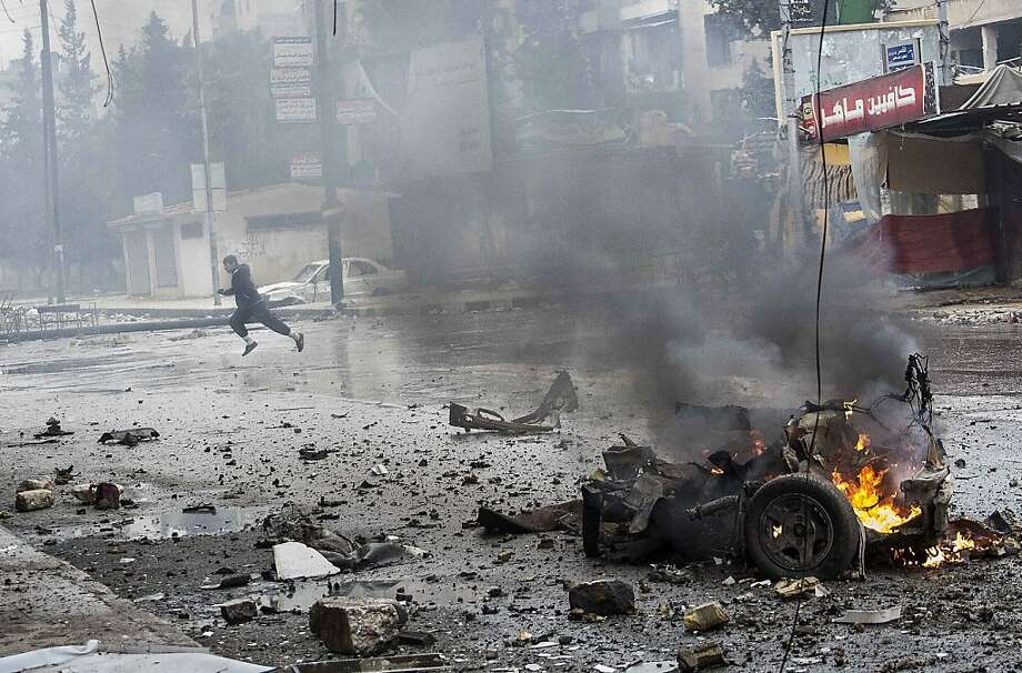 In this Monday, Dec. 17, 2012 photo, a boy runs for cover after a mortar shell hit a street killing several people in the Bustan Al-Qasr district of Aleppo, Syria. (AP Photo/Narciso Contreras) Photo: Narciso Contreras, Associated Press