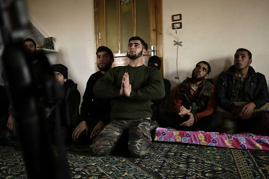 In this Monday, Dec. 17, 2012 photo, Syrian rebels listen to their trainer while teaching them how to use the RPG during a training session in Maaret Ikhwan, near Idlib, Syria. The training is part of an attempt to transform the rag-tag rebel groups into a disciplined fighting force. (AP Photo/Muhammed Muheisen) Photo: Muhammed Muheisen, Associated Press