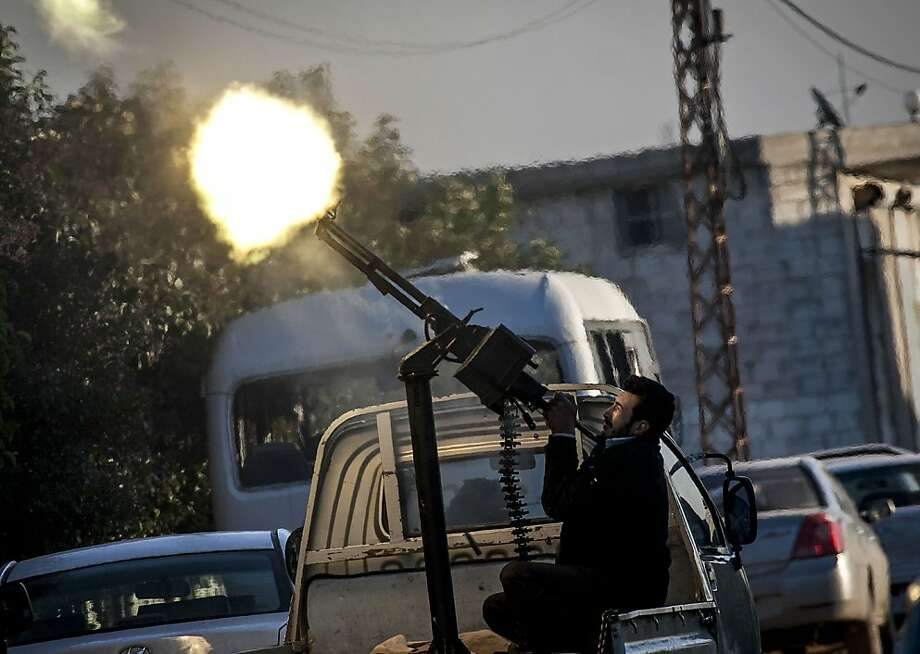 In this Saturday, Dec. 15, 2012 photo, A Free Syrian Army fighter fires a weapon during heavy clashes with government forces at a academy besieged by rebels north of Aleppo, Syria. (AP Photo/Narciso Contreras) Photo: Narciso Contreras, Associated Press