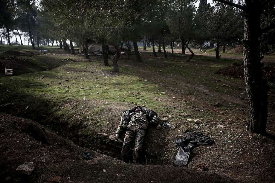 This Sunday, Dec. 16, 2012 photo, shows the lifeless body of a Syrian army soldier who was killed during heavy clashes with Free Syrian Army fighters at a military academy besieged by rebels north of Aleppo, Syria. (AP Photo/Narciso Contreras) Photo: Narciso Contreras, Associated Press