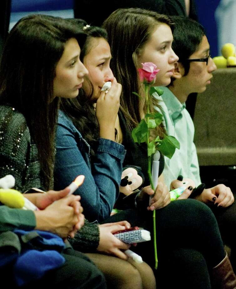 A large gathering at the O'Neill Center in Danbury listens to speakers, and watches a slide presentation of the Sandy Hook victims during the Tribute to Newtown program. Wednesday, Dec. 19, 2012 Photo: Scott Mullin