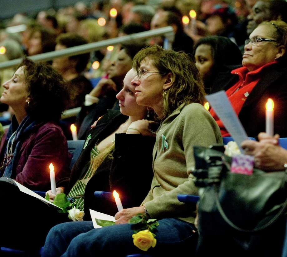 A large gathering at the O'Neill Center in Danbury watches a slide presentation of the Sandy Hook victims during the Tribute to Newtown program. Wednesday, Dec. 19, 2012 Photo: Scott Mullin