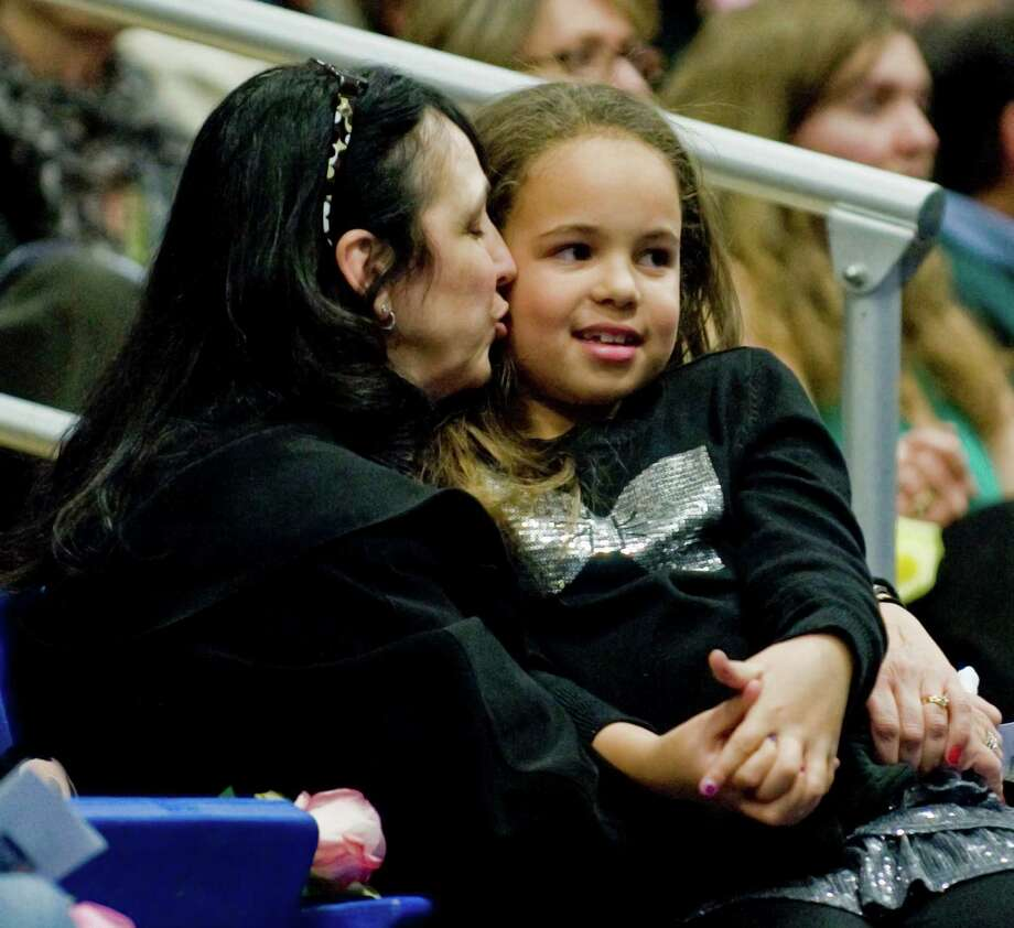 Deddie Hyde of Danbury kisses her granddaughter Alexis Johnson, 9, as they listen to various speakers at the O'Neill Center in Danbury during the Tribute to Newtown program. Wednesday, Dec. 19, 2012 Photo: Scott Mullin / The News-Times Freelance