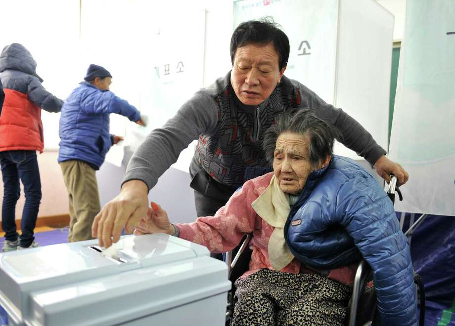 An elderly South Korean woman (R) is helped as she casts her vote in the presidential election at a polling station in Nonsan, 150 kms south of Seoul, on December 19, 2012. South Koreans went to the polls on December 19 to choose a new president in a close and potentially historic election that could result in Asia's fourth-largest economy getting its first female leader.  AFP PHOTO / JUNG YEON-JEJUNG YEON-JE/AFP/Getty Images Photo: JUNG YEON-JE, Staff / AFP