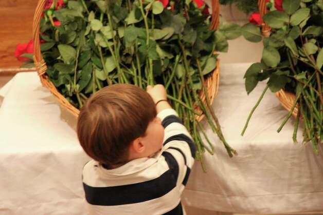 Will Pullen, 5, places a rose in a basket in remembrance of those lost in the Newtown tragedy where 26 lives were lost. Dec. 19, 2012. Photo: Megan Davis