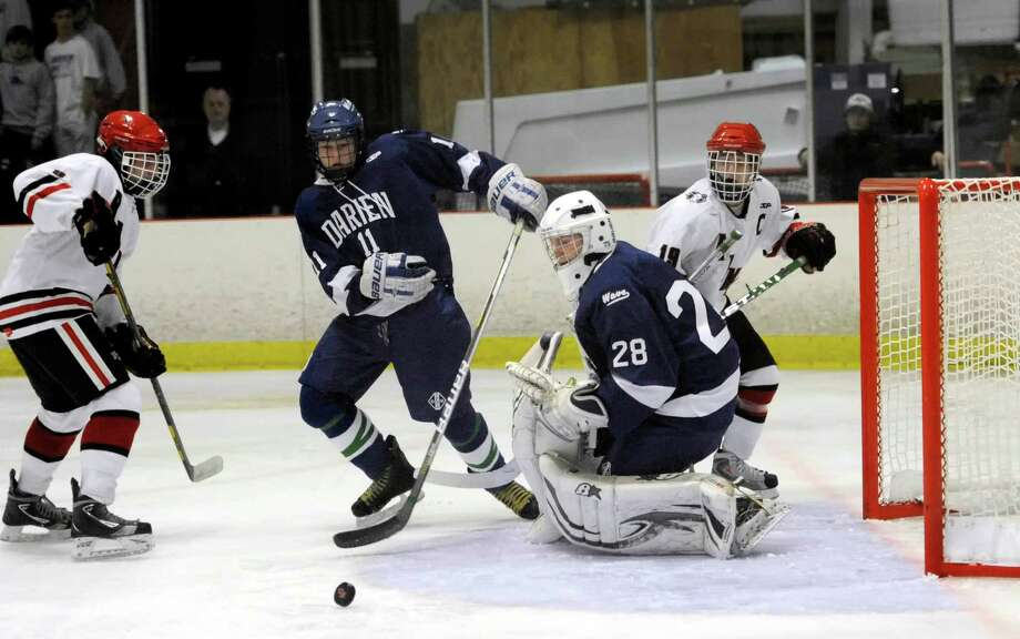 New Canaan high school's Peter Reinhardt (left) and Henry Stanton (right) put pressure on the Darien high school goalie Michael Collins and defenseman Nicholas Tuzinkiewicz towards the end of an overtime period in a boys ice hockey game player at the Darien Ice Rink, Darien CT on Wednesday, December 19th, 2012. Photo: Mark Conrad / Stamford Advocate Freelance