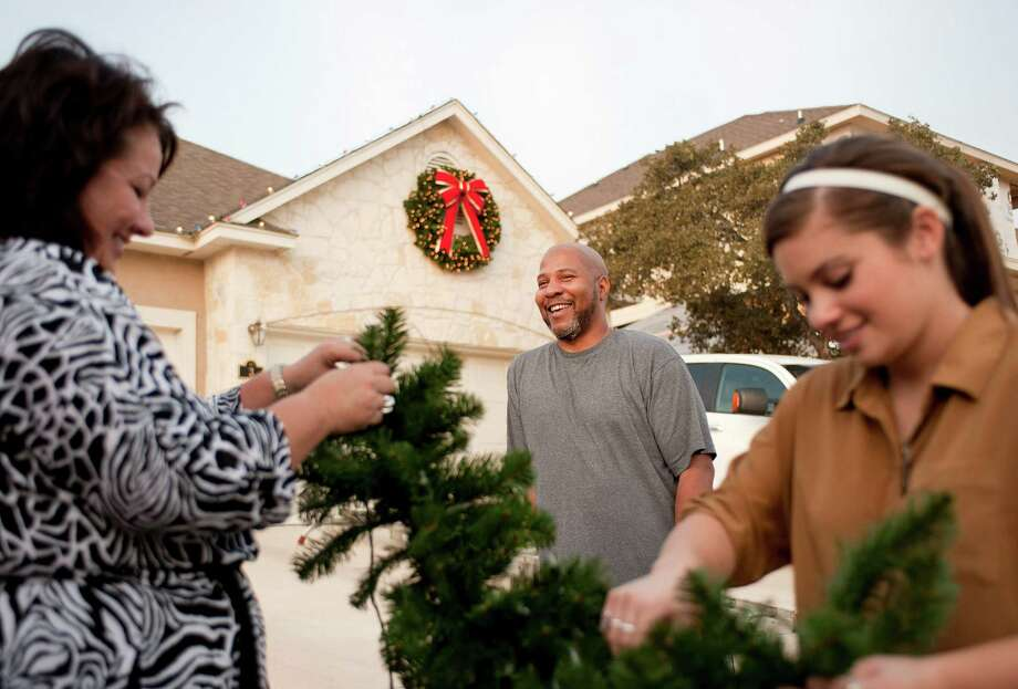 Air Force 1st Lt. Phillip Garrette, center, smiles as Tammy Sheffield, left, and daughter Kelsey Sheffield, of Christmas Decor Holiday and Event Lighting, arrange garland for Garrette's home, Wednesday, Dec. 19, 2012, in San Antonio. Photo: Darren Abate, Darren Abate/For The Express-New