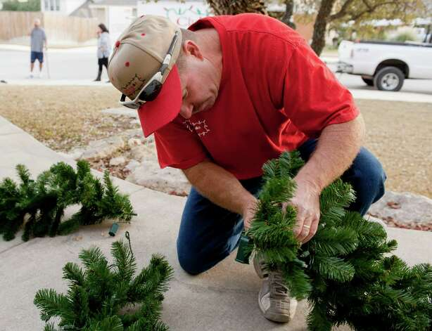 Casey Sheffield, of Christmas Decor Holiday and Event Lighting, arranges garland for the Garrette family home, Wednesday, Dec. 19, 2012, in San Antonio. Photo: Darren Abate, Darren Abate/For The Express-New