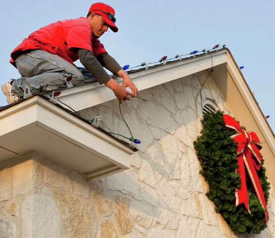Jose Padilla, of Christmas Decor Holiday and Event Lighting, installs lights on the Garrette family home, Wednesday, Dec. 19, 2012, in San Antonio. Photo: Darren Abate, Darren Abate/For The Express-New