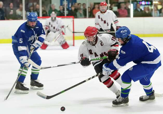 New Canaan high school's Henry Stanton (center) tries to get by Darien high school's Brendan Cassidy (right) in a boys ice hockey game player at the Darien Ice Rink, Darien CT on Wednesday, December 19th, 2012. Photo: Mark Conrad / Stamford Advocate Freelance