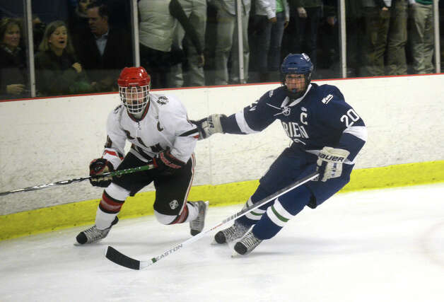 Darien's Trent Bergin (20) and New Canaan's Henry Stanton (19) on the ice during the boys ice hockey game at the Darien Ice Rink on Wednesday, Dec. 19, 2012. Photo: Amy Mortensen / Connecticut Post Freelance