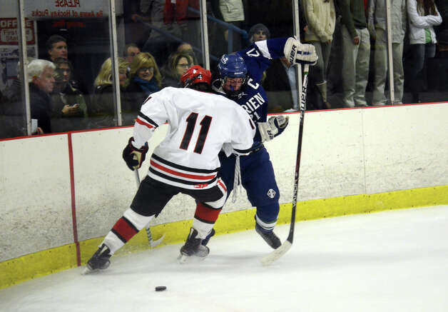 Darien's Brendan Hathaway (21) and New Canaan's John O'Rourke (11) look for the puck during the boys ice hockey game at the Darien Ice Rink on Wednesday, Dec. 19, 2012. Photo: Amy Mortensen / Connecticut Post Freelance