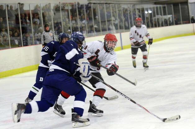 New Canaan's Peter Reinhardt (9) takes a shot on goal during the boys ice hockey game against Darien at the Darien Ice Rink on Wednesday, Dec. 19, 2012. Photo: Amy Mortensen / Connecticut Post Freelance