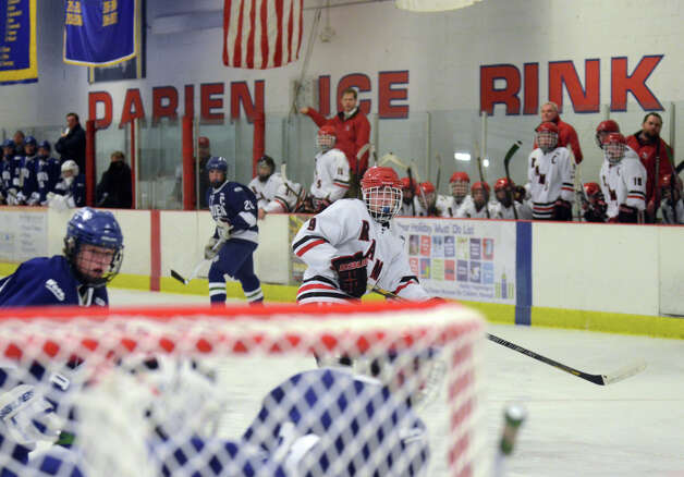 New Canaan's Peter Reinhardt (9) tracks the puck after taking a shot during the boys ice hockey game against Darien at the Darien Ice Rink on Wednesday, Dec. 19, 2012. Photo: Amy Mortensen / Connecticut Post Freelance