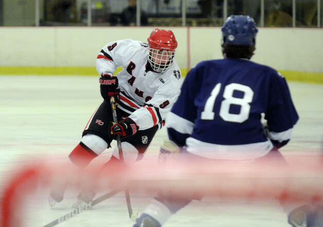 New Canaan's Peter Reinhardt (9) controls the puck as Darien's Kevin Love (18) defends during the boys ice hockey game at the Darien Ice Rink on Wednesday, Dec. 19, 2012. Photo: Amy Mortensen / Connecticut Post Freelance