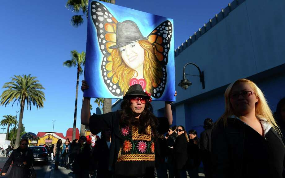 A woman carries a painting as fans of the late singer Jenni Rivera wait in line with their tickets to attend the memorial service in California on Wednesday. Photo: FREDERIC J. BROWN, Staff / AFP