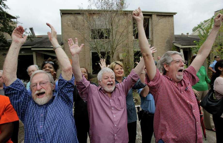 From left, Miles Frey, Mike Alexander and Gary Ward, who all live near the former Inwood Oaks complex, cheer as Mayor Annise Parker begins the demolition of the apartments on Wednesday. Photo: Melissa Phillip, Houston Chronicle / © 2012 Houston Chronicle