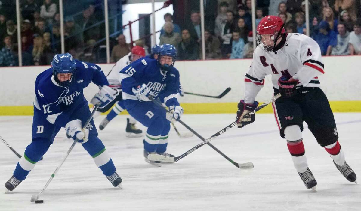 Darien high school's Tiger Sullivan about to take a shot on goal in a boys ice hockey game against New Canaan high school at the Darien Ice Rink, Darien CT on Wednesday, December 19th, 2012. New Canaan high school defenseman John McMahon (right)