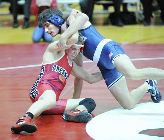 At right, Eric Strazza of Wilton gets the best of Ben Jones of Greenwich in a match Strazza won in the 132 pound class during boys high school wrestling match at Greenwich High School, Wednesday night, Dec. 19, 2012. Photo: Bob Luckey / Greenwich Time