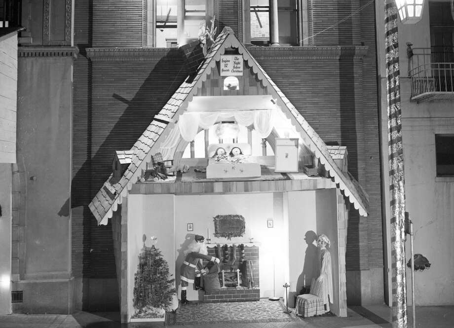 I love the simplicity and the lighting in this display, which includes a living room scene and two kids in the loft. I'm assuming if there was a real fire at this moment, the truck would burst through the chimney and run over Santa ... (Art Frisch / The Chronicle)