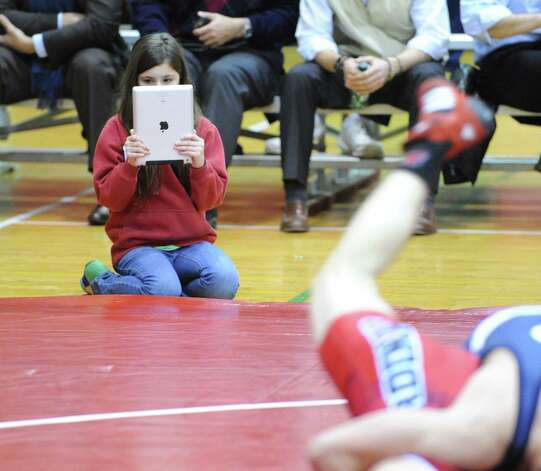 A wrestling fan uses her iPad to videotape a match during boys high school wrestling match at Greenwich High School, Wednesday night, Dec. 19, 2012. Photo: Bob Luckey / Greenwich Time