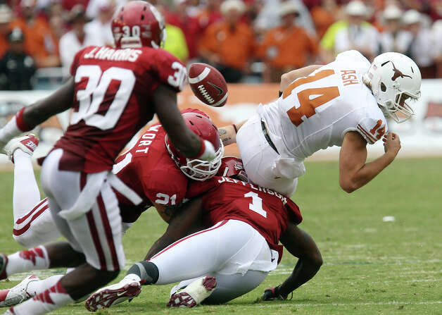 Texas Longhorns quarterback David Ash (14) fumbles the ball while tackled by Oklahoma Sooners' Tom Wort (21) and Tony Jefferson (01) in the second half at the Red River Rivalry at the Cotton Bowl in Dallas on Saturday, Oct. 13, 2012. The Sooners defeated the Longhorns 63-21. Photo: Kin Man Hui, San Antonio Express-News / © 2012 San Antonio Express-News