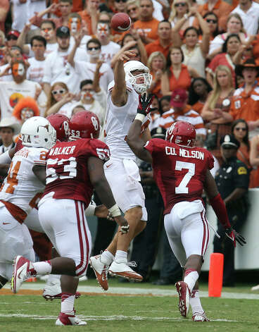 Texas Longhorns' quarterback David Ash (center) attempts a throw over Oklahoma Sooners' Casey Walker (53) and Corey Nelson (07) in the second half at the Red River Rivalry at the Cotton Bowl in Dallas on Saturday, Oct. 13, 2012. The Sooners defeated the Longhorns 63-21. Photo: Kin Man Hui, San Antonio Express-News / © 2012 San Antonio Express-News