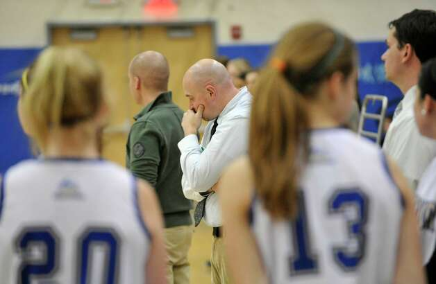 Newtown girls basketball head coach Jeremy O'Connell, center, stands on the sideline before the Nighthawk's game against Masuk on Wednesday, Dec. 19, 2012. Wednesday's basketball game was the first sporting event since the Sandy Hook Elementary School shooting. Photo: Jason Rearick / The News-Times