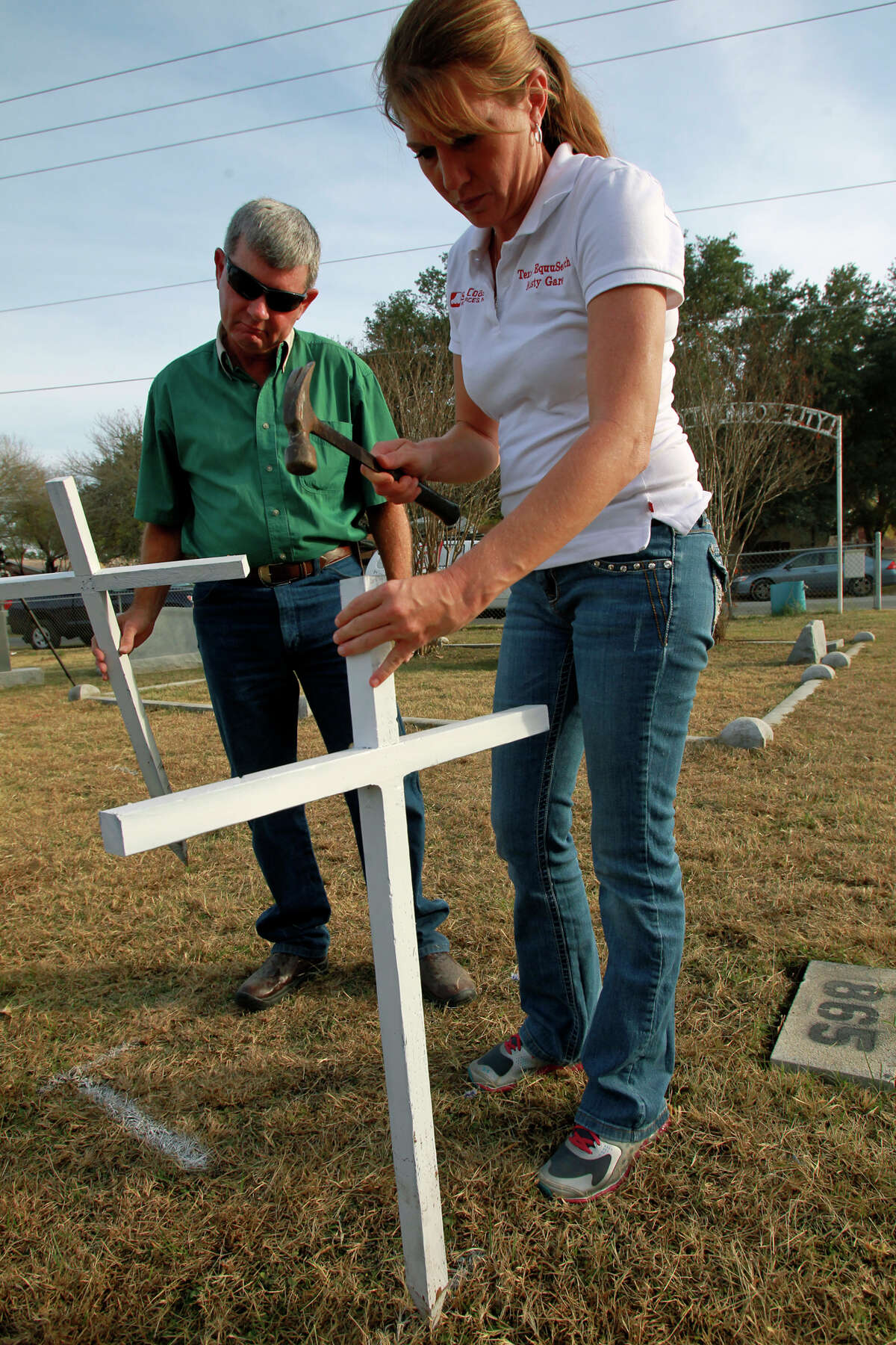 Glenn Norton, a Lytle United Methodist Church trustee, and Misty Garey of Texas EquuSearch erect crosses for the two Rudasill children Wednesday.