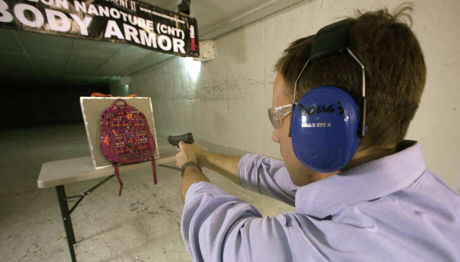 Rick Brand, chief operating officer of Amendment II, fires a 9mm pistol into a children's backpack with an anti-ballistic insert in Taylorsville, Utah. Anxious parents are fueling sales of armored backpacks for children. Photo: Rick Bowmer, STF / AP