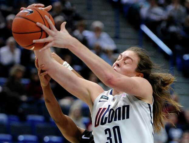 Connecticut's Breanna Stewart, right, grabs a rebound from Oakland's Victoria Lipscomb during the second half of an NCAA college basketball game in Hartford, Conn., Wednesday, Dec. 19, 2012. Stewart scored 21 points and had 13 rebounds in her team's 97-25 victory. (AP Photo/Fred Beckham) Photo: Fred Beckham, Associated Press / FR153656 AP